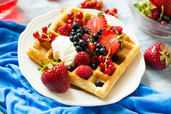 Healthy breakfast: Belgian waffles with sour cream, strawberry, raspberry, blueberry, cherry and red currant Royalty Free Stock Photos