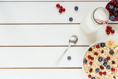 Healthy breakfast with berries and milk on the white wooden table with copy space, top view royalty free stock photos
