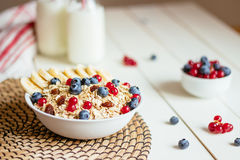 Healthy breakfast with berries and milk on the white wooden table stock photo