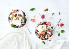 Healthy breakfast. Berry crumble with fresh blueberries, raspberries, strawberries, almond, walnuts, pecans, yogurt, and mint in ceramic plates over white Stock Photo
