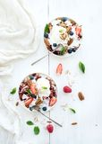 Healthy breakfast. Berry crumble with fresh. Blueberries, raspberries, strawberries, almond, walnuts, pecans, yogurt, and mint in ceramic plates over white Stock Photos
