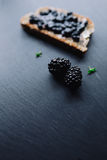 Healthy breakfast with blackberry jam. With toast on black slate background Royalty Free Stock Image