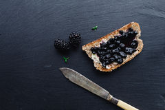 Healthy breakfast with blackberry jam. With toast on black slate background Royalty Free Stock Photography