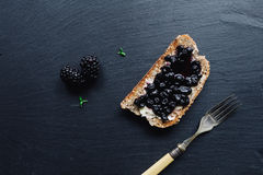 Healthy breakfast with blackberry jam. With toast on black slate background royalty free stock photos