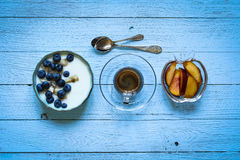 Healthy Breakfast with blueberries and banana yogurt. Biscuits, marmalade, coffee and peaches over a light wooden background Royalty Free Stock Photos