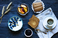 Healthy Breakfast with blueberries and banana yogurt. Biscuits, marmalade, coffee and peaches over a light wooden background Royalty Free Stock Photography