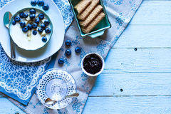 Healthy Breakfast with blueberries and banana yogurt. Biscuits, marmalade, coffee and peaches over a light wooden background Stock Photo