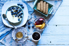 Healthy Breakfast with blueberries and banana yogurt. Biscuits, marmalade, coffee and peaches over a light wooden background Royalty Free Stock Photo