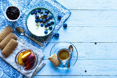 Healthy Breakfast with blueberries and banana yogurt. Biscuits, marmalade, coffee and peaches over a light wooden background Stock Image