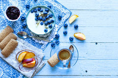 Healthy Breakfast with blueberries and banana yogurt. Biscuits, marmalade, coffee and peaches over a light wooden background Stock Images