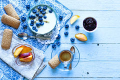 Healthy Breakfast with blueberries and banana yogurt. Biscuits, marmalade, coffee and peaches over a light wooden background Royalty Free Stock Image