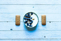 Healthy Breakfast with blueberries and banana yogurt. Biscuits, marmalade, coffee and peaches over a light wooden background Stock Photos