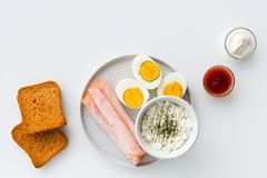 Healthy breakfast. Boiled eggs, ham and fresh cheese sprinkled w stock photo