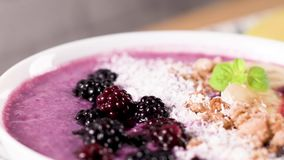 Healthy breakfast bowl. Blueberry smoothie with banana, cococnut and blackberries stock video