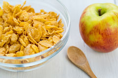 Healthy breakfast, bowl of cereal and apple. Healthy breakfast, bowl of cereal, apple and a small wooden spoon on a light wooden background Royalty Free Stock Images