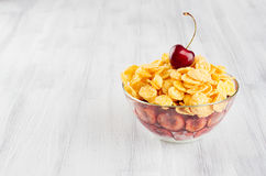 Healthy breakfast in bowl with golden corn flakes decorated cherry on white wood board. Royalty Free Stock Image