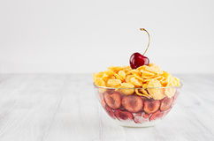 Healthy breakfast in bowl with golden corn flakes decorated cherry on white wood board. Decorative border with copy space. Royalty Free Stock Image