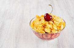 Healthy breakfast in bowl with golden corn flakes, ripe slice cherry on white wood board. Decorative border with copy space. Stock Image