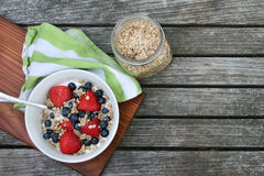 Healthy Breakfast Bowl. Granola in white bowl with greek yogurt and berries on wooden background, top view, copy space Royalty Free Stock Photos
