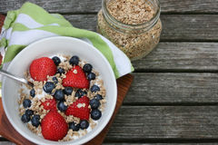 Healthy Breakfast Bowl. Granola in white bowl with greek yogurt and berries on wooden background, top view, text space Stock Photos