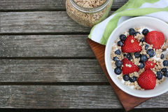 Healthy Breakfast Bowl. Granola in white bowl with greek yogurt and berries on wooden background, top view, type space Stock Image