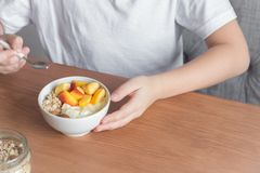 Healthy breakfast bowl in hands. Eating healthy breakfast bowl. Oatmeal granola, yougurt, fresh nectarins in white bowl in female child hands over wooden table Royalty Free Stock Photos