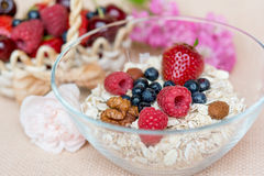 Healthy breakfast. A bowl with hole grain flakes, berries, nuts and rose on sackcloth, beige background. Healthy breakfast Royalty Free Stock Photography