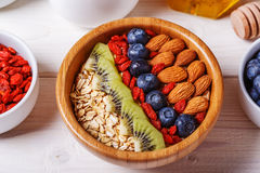 Healthy breakfast - bowl of oat flakes with fresh fruit, almond. And honey, selective focus Royalty Free Stock Image