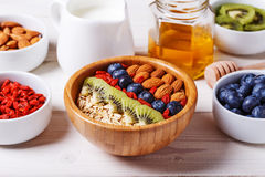 Healthy breakfast - bowl of oat flakes with fresh fruit, almond. And honey, selective focus Royalty Free Stock Images