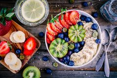 Breakfast bowl: oatmeal with banana, kiwi, strawberry, blueberries and chia seeds royalty free stock image