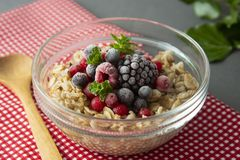 Healthy breakfast in a bowl with oatmeals, frozen berries, fresh strawberries, mint. Oat porridge with fruits royalty free stock image