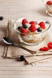 Healthy breakfast. Bowl with raspberries and blueberries. Raspberries, blueberries, cereals and yogurt in a glass bowl on sackcloth and wooden slats. Healthy Royalty Free Stock Image