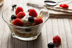 Healthy breakfast. Bowl with raspberries and blueberries. Raspberries, blueberries, cereals and yogurt in a glass bowl on wooden slats. Healthy breakfast for a Royalty Free Stock Photos