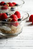 Healthy breakfast. Bowl with raspberries and blueberries. Raspberries, blueberries, cereals and yogurt in a glass bowl on wooden slats. Healthy breakfast for a Stock Photography