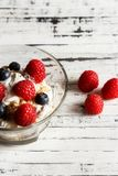 Healthy breakfast. Bowl with raspberries and blueberries. Raspberries, blueberries, cereals and yogurt in a glass bowl on wooden slats. Healthy breakfast for a Stock Image
