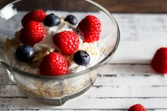 Healthy breakfast. Bowl with raspberries and blueberries. Raspberries, blueberries, cereals and yogurt in a glass bowl on wooden slats. Healthy breakfast for a Stock Photos