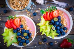 Healthy breakfast bowl: raspberry smoothies with granola, blueberries, strawberries and carambola. Healthy breakfast bowl: raspberry smoothies with granola stock photo