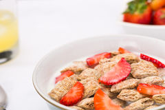 Healthy Breakfast. Bowl of wheat with strawberries, milk, and a bowl of strawberries with a glass of orange juice Royalty Free Stock Images
