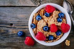 A healthy breakfast bowl. Whole grain cereal with fresh blueberries and raspberries on wooden background. Top view. A healthy breakfast bowl. Whole grain cereal Stock Image