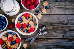 A healthy breakfast bowl. Whole grain cereal with fresh blueberries and raspberries on wooden background. Top view. A healthy breakfast bowl. Whole grain cereal Royalty Free Stock Photo