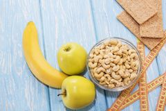 Healthy breakfast. Cashew nuts in a white bowl. Green Apple, banana. Humor. Male potency. Healthy breakfast. Cashew nuts in a white bowl. Green Apple, banana Stock Photography
