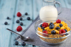 Healthy breakfast cereal with berries and milk. On a light blue wooden background Stock Photography