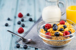Healthy breakfast cereal with berries, milk and orange juice. On a light blue wooden background Stock Photography