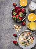 Healthy breakfast cereal with dried fruits, fresh orange juice, a plate of strawberries wooden rustic background top view Stock Image