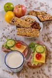 Healthy breakfast including cereal bars, fruits and vegetables. Healthy breakfast, cereal sticks in mycelium with nuts, two pans of vegetables laid on the table royalty free stock images