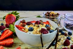 Healthy breakfast, cereal with yoghurt, strawberries, blueberries, raspberries and muesli on wooden rustic background royalty free stock photography