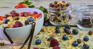 Healthy breakfast, cereal with yoghurt, strawberries, blueberries, raspberries and muesli on wooden rustic background. Concept of: fitness, diet, wellness and royalty free stock photo
