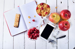 Healthy breakfast cereals, berries, apples and cereal bars on a. Table top view.Concept of healthy food, accessories for recording diet: a smartphone, notebook Stock Image