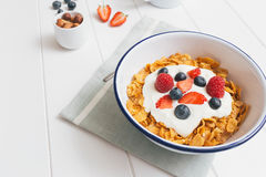 Healthy breakfast with cereals and berries in an e. Top view of healthy breakfast with cerelas, berries, honey and nuts in an enamel bowl on a white wood Stock Photos