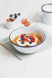 Healthy breakfast with cereals and berries in an e. Top view of healthy breakfast with cerelas, berries, honey and nuts in an enamel bowl on a white wood royalty free stock photography